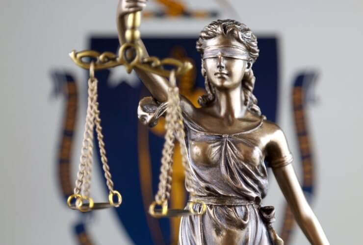 Scales of Justice with Massachusetts court flag behind it
